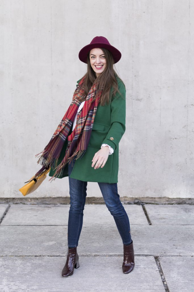 green coat mustard bag cold smile girl in burgundy hat and blue jeans