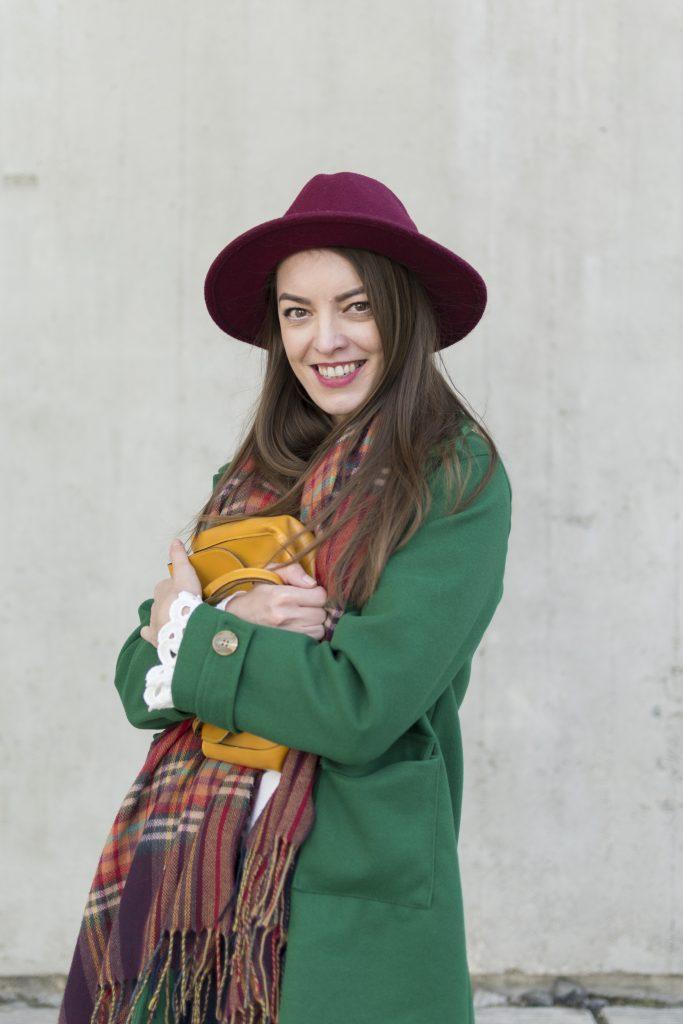 green coat mustard bag cold smile girl in burgundy hat