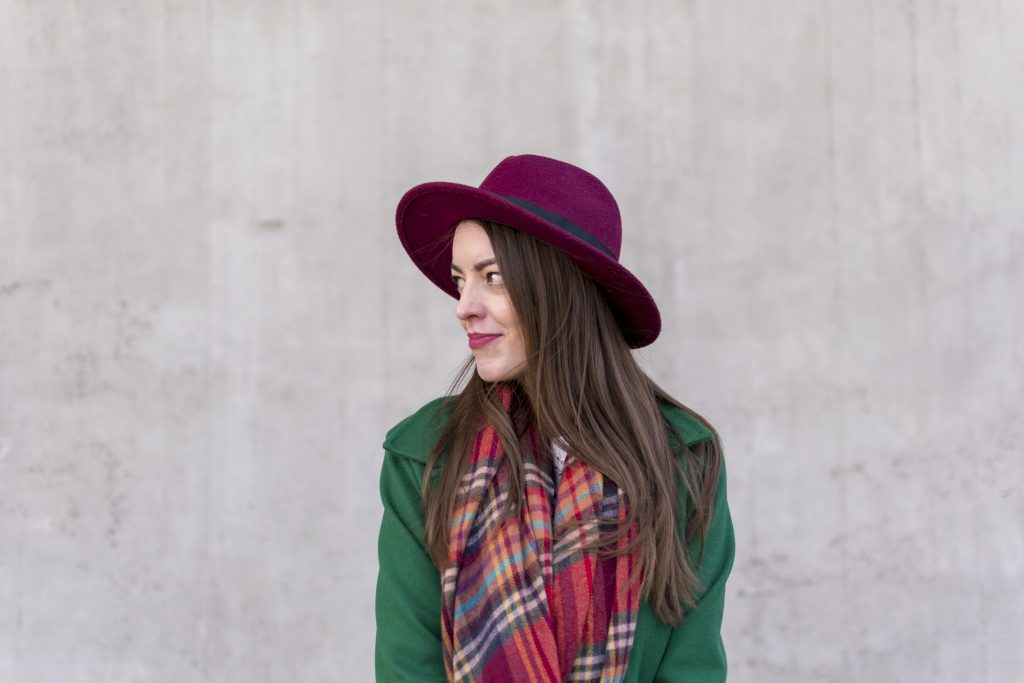 smile girl with brown hair in burgundy hat and green coat